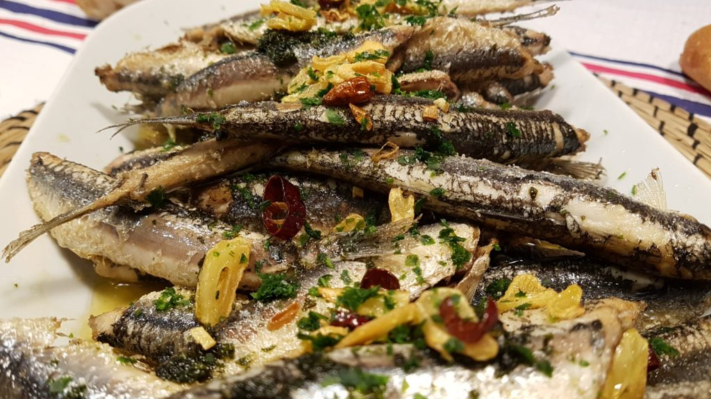 Crispy fried anchovies in olive oil with garlic and cayenne pepper, topped with fresh parsley