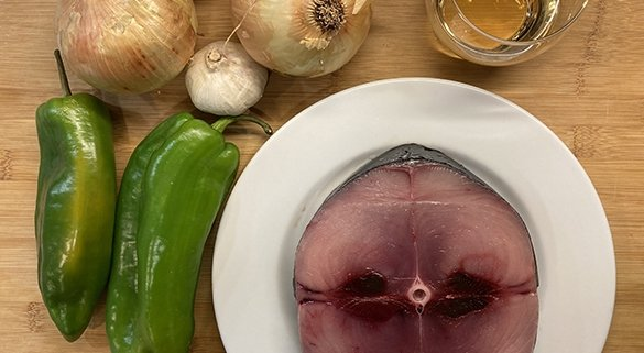 A steak of bonito white tuna, onions, green peppers, garlic bulb and a glass of txakoli wine