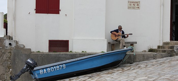 Man playing the guitar at the port of Getary on the French Basque Coast on