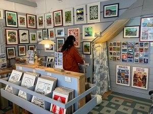 Basque souvenirs and gifts: A woman looking through Basque illustrations and prints in a shop in St. Jean de Luz