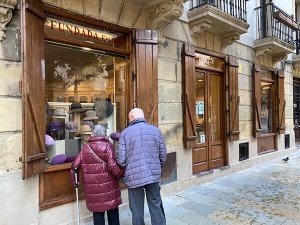 Basque souvenirs and gifts: Two people looking at the window display of Casa Ponsol Basque beret shop in San Sebastian